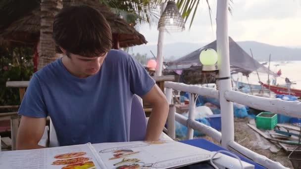 Junger Mann sitzt in einem Café am Strand bei einem Sonnenuntergang, scrollt durch das Menü, eine Wahl zu treffen will. Slow-Motion. HD, 1920 x 1080