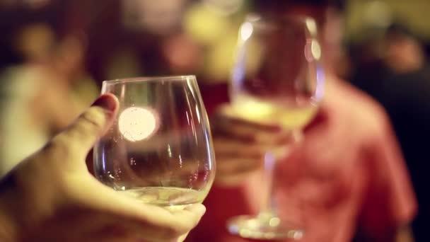 Pár sedí v kavárně a cinkání sklenic s bílým vínem na světlém pozadí rozmazané bokeh. 1920 × 1080
