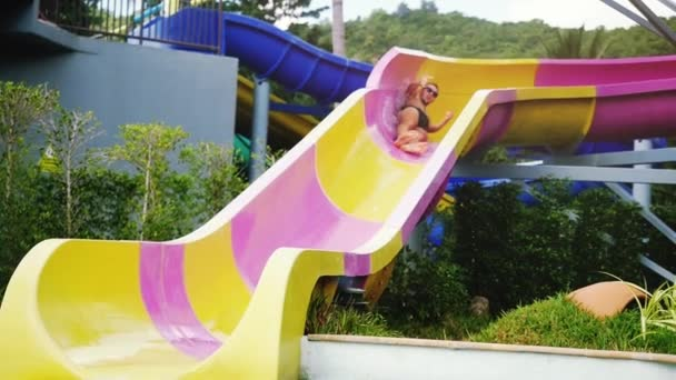 Excited man in sunglasses sliding down the fast water slide in fun aqua park screaming on a hot summer day. slow motion. 1920x1080