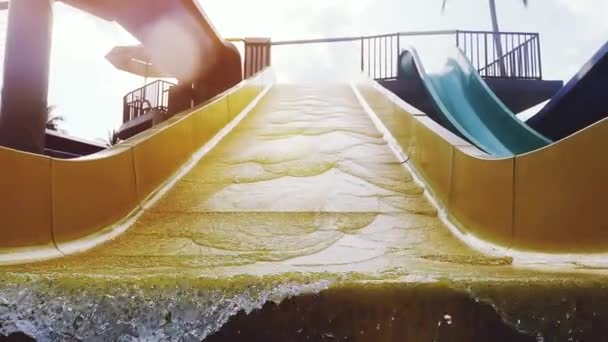 Water flow pouring water yellow waterslide in aquapark during sunset with lens flare effects in slow motion. 1920x1080