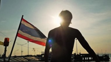 Back view ofyoung man standing on pier next to thai flag enjoying sunny day during amazing sunset with lens flare effects. slow motion. 1920x1080