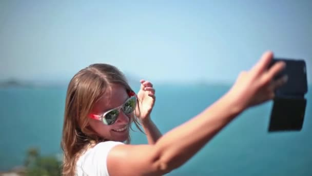 Cheerful young woman having fun taking smartphone selfie pictures of herself on beach. Style girl model wearing fashion sunglasses. 1920x1080