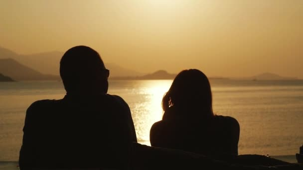 Couple romantic relaxing on beach looking at amazing sunset at honeymoon travel vacation. slow motion. 1920x1080