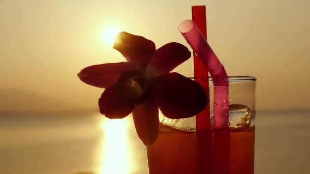 Sklo tropickém koktejlu zdobeny květina na úžasný západ slunce a krásné moře na pozadí. Zpomalený pohyb. 1920 × 1080