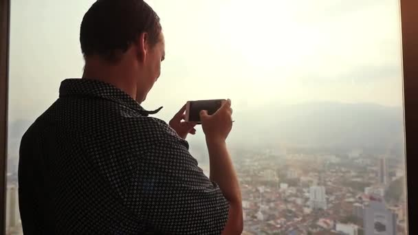 Businessman takes photo with cellphone next to window at amazing sunset and beautiful city view. slow motion. 1920x1080