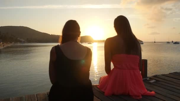 Young girls sitting on the pier looks amazing sunset and talking. Sunset sea of tropical island. slow motion. 1920x1080