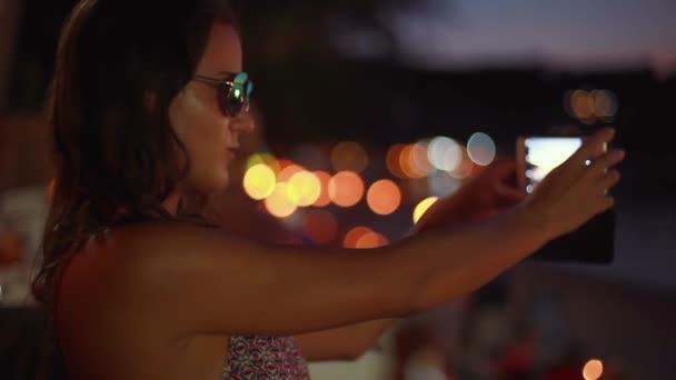 Portrét mladé ženy bruneta v sluneční brýle představují vytváření tváře pořízení selfie fotografie pomocí smartphone s bokeh světly v beach café. 1920 × 1080
