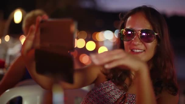 2a3b7c53b0 Close up of portrait of young beautiful brunette woman in sunglasses posing  making faces taking selfie photo using smartphone with bokeh lights in beach  ...