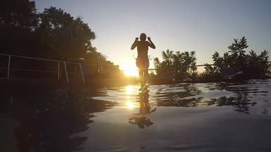 Young woman jumps in swimming pool at amazing sunset through the sun with lens flare effects. slow motion. 1920x1080