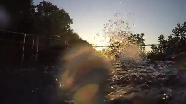 Young man splashing water in swimming pool in slow motion through the sun and sunshine during amazing sunset on tropical resort. 1920x1080