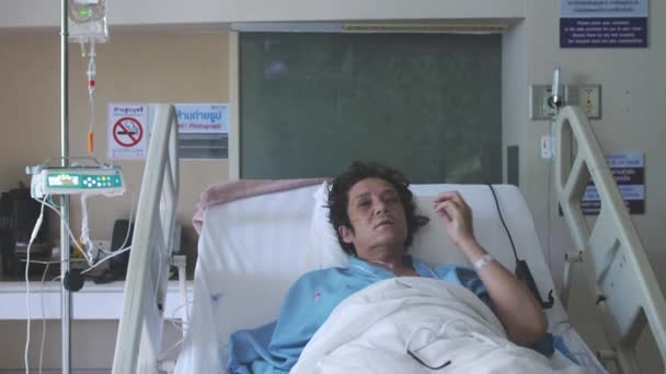 Sick woman in aged lies in a hospital bed with an oxygen mask under a drip. 1920x1080