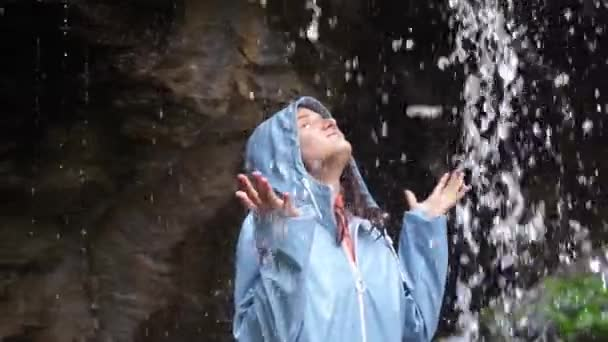 Young cheerful woman arms outstretched behind spectacular waterfall. Young woman outstretching arms by majestic waterfall. slow motion