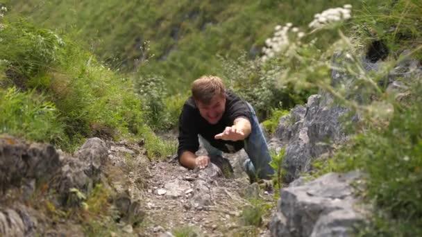 Muž vyleze na skalní pokus dostat se na vrchol útesu