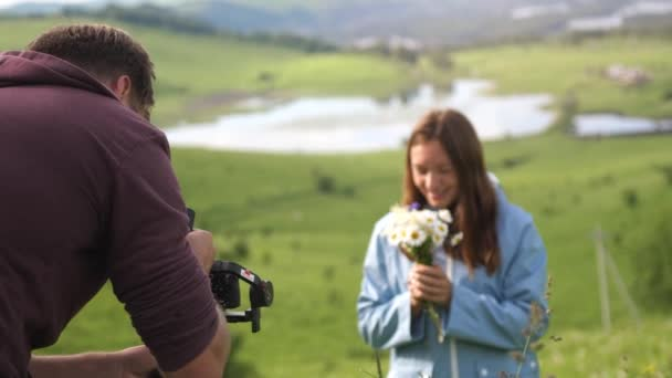 Turisté pár těší přírodu, mladý muž fotí šťastnou ženu drží kytice polních květin. zpomalený pohyb