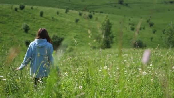 Tourist takes video of young walking woman in a field