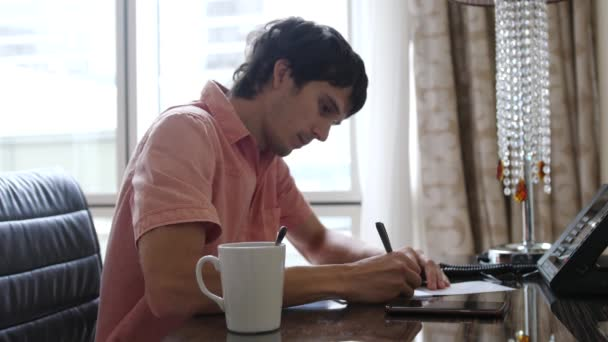 Male writer works sitting at the desk with coffee. A man writes on paper, typewriter is in front of him