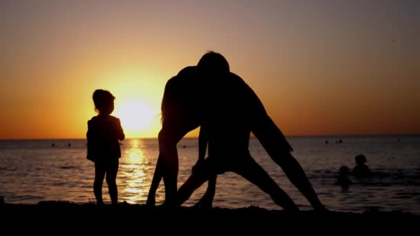 Happy family mother with children on vacation at the beach during sunset.