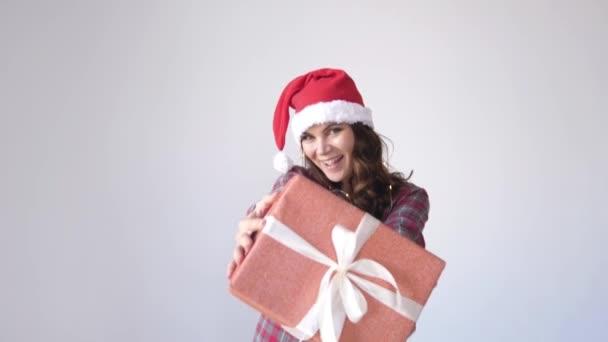 Boldog lány karácsonyi sapkában ad egy ajándék doboz fehér alapon. Kis ajándék női kézben. Ünnepi csomagolás, csomagolás.