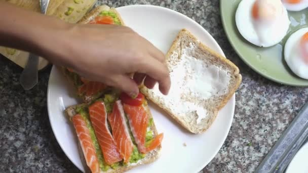 Cooking Toasts with avocado, tomato and smoked salmon on the white plate