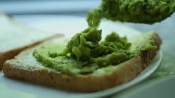 namazat avokádo na opečený chléb. Dělám chutné avokádové toasty k snídani