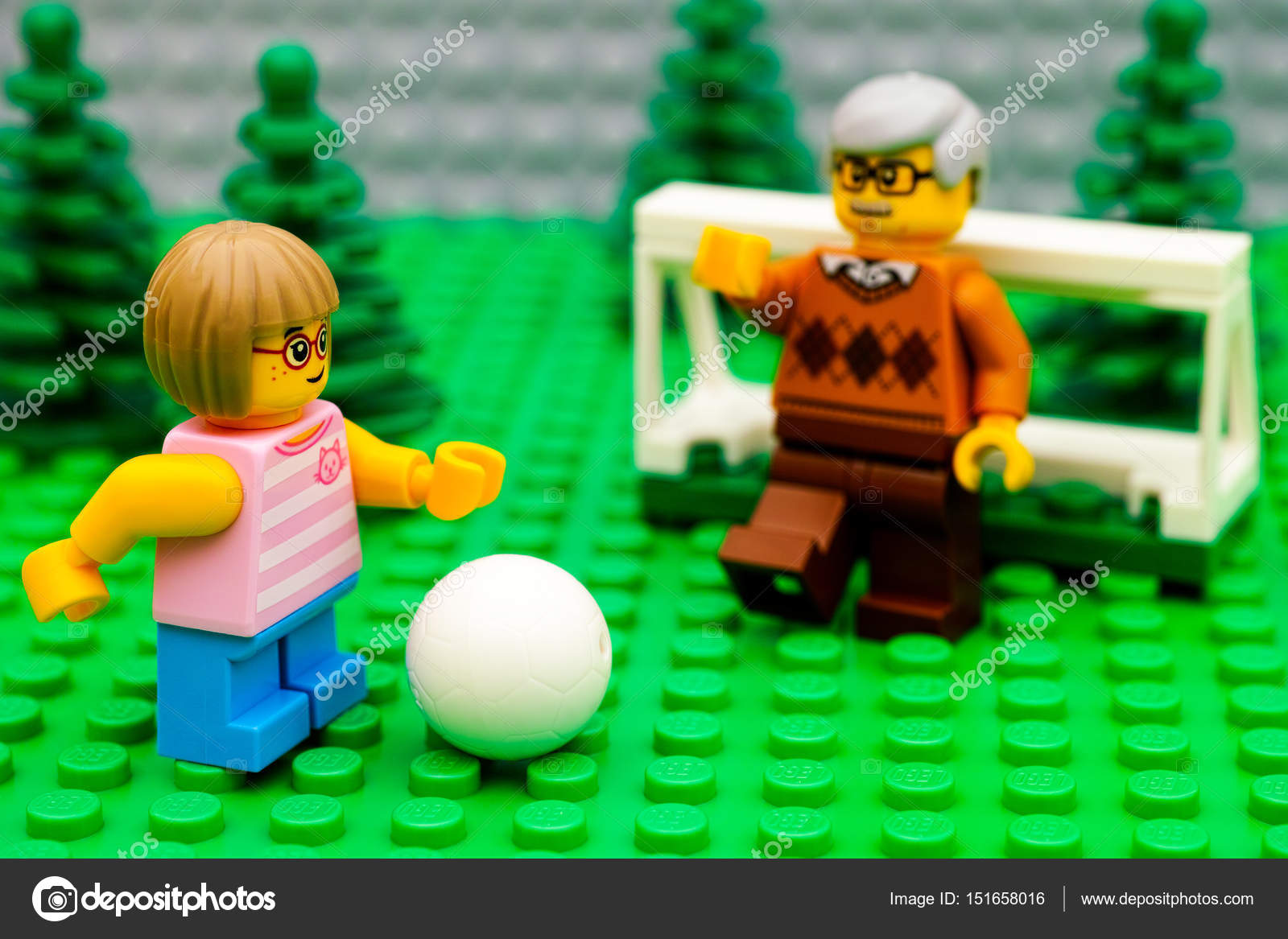 Lego girl playing football with her grandfather in park — Stock Photo