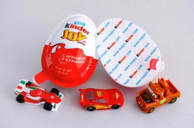 Kinder Joy eggs with three Kinder Cars toys on gray background