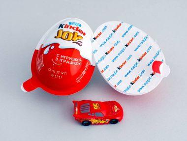 Kinder Joy eggs with Kinder car toy on gray background