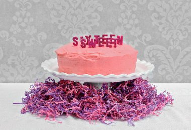 A pretty pink birthday layer cake with Sweet Sixteen spelled out on top in glitter candles.  Cake is on pedestal and surrounde stock vector