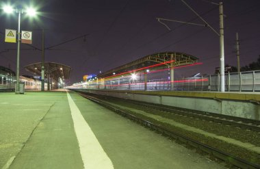 Train on Moscow passenger platform (Savelovsky railway station) is one of the nine main railway stations in Moscow, Russia (at night)