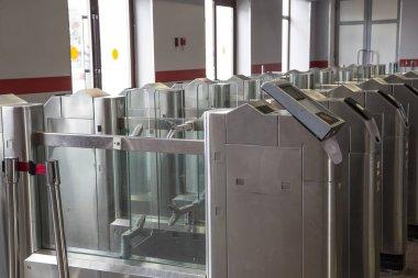 Modern metallic turnstile gate, entrance of railway station. Moscow, Russia
