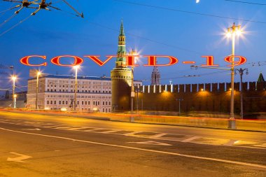 Coronavirus in Moscow, Russia. Night view of the Kremlin. Covid-19 sign. Concept of COVID pandemic and travel.