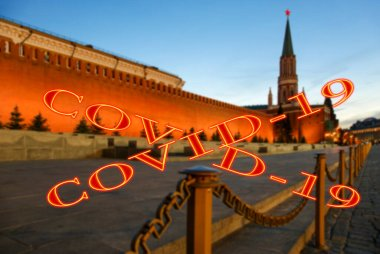 Coronavirus in Moscow, Russia. Night view of the Kremlin. Covid-19 sign on a blurred background. Concept of COVID pandemic and travel.