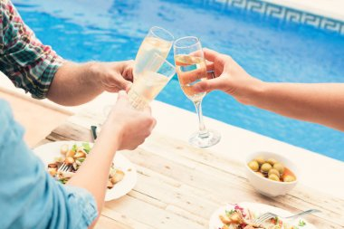 Friends toasting at party by swimming pool