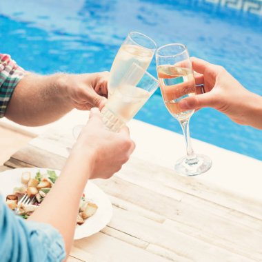 Friends having wine at party by swimming pool