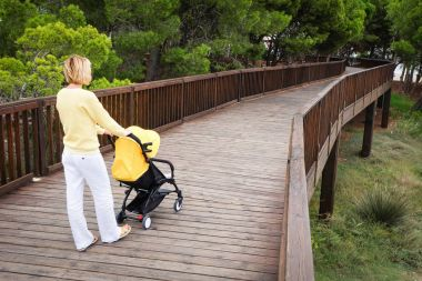 Young woman strolling a baby carriage on wooden bridge