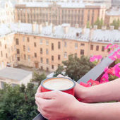 Fotografie Woman drinking coffee on balcony