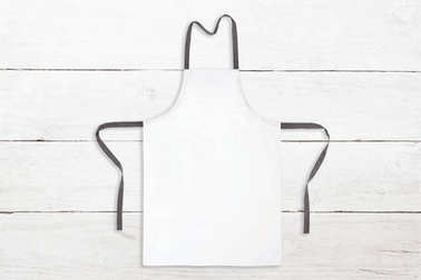 Blank white apron on wooden background