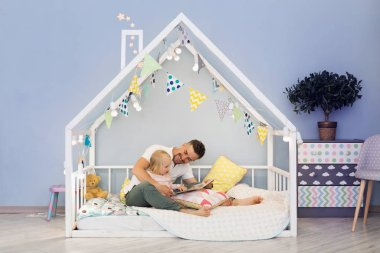 Happy father dad in cute house bed with blonde daughter reading stories at bedtime