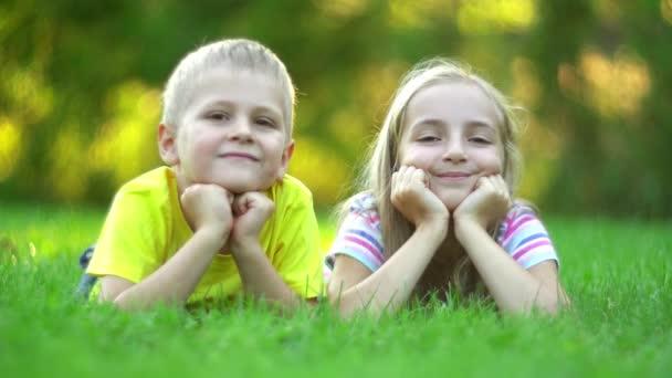 Děti leží na zelené trávě