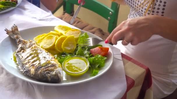 dorada smažených ryb na talíři s brambory a zeleninou