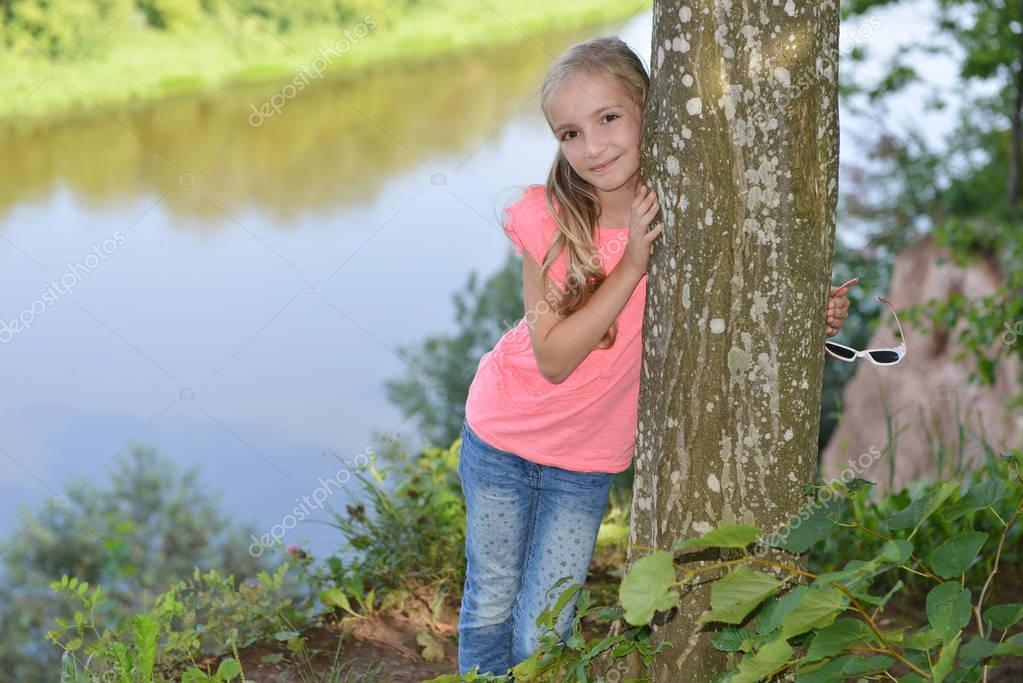 Young Blonde Girl Green Eyes Shows Tree Near River 1