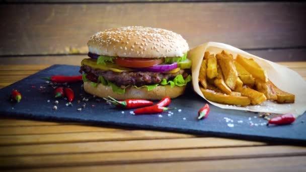 Chutné domácí hamburger s brambory, podávané na kamennou desku