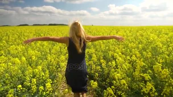 young blonde woman posing in beautiful rapeseed field
