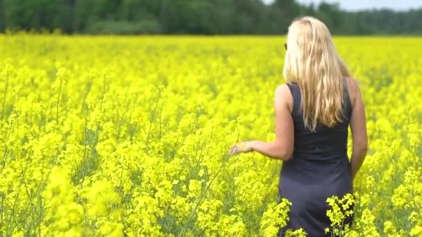 Mladá blondýnka pózuje v krásném řepkové pole