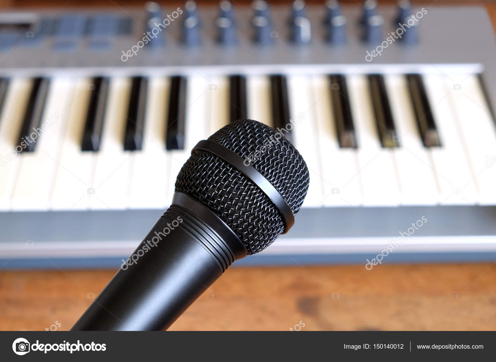 Black vocal microphone closeup against electronic synthesizer