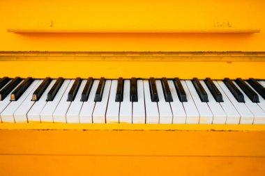 Yellow vintage piano, closeup view