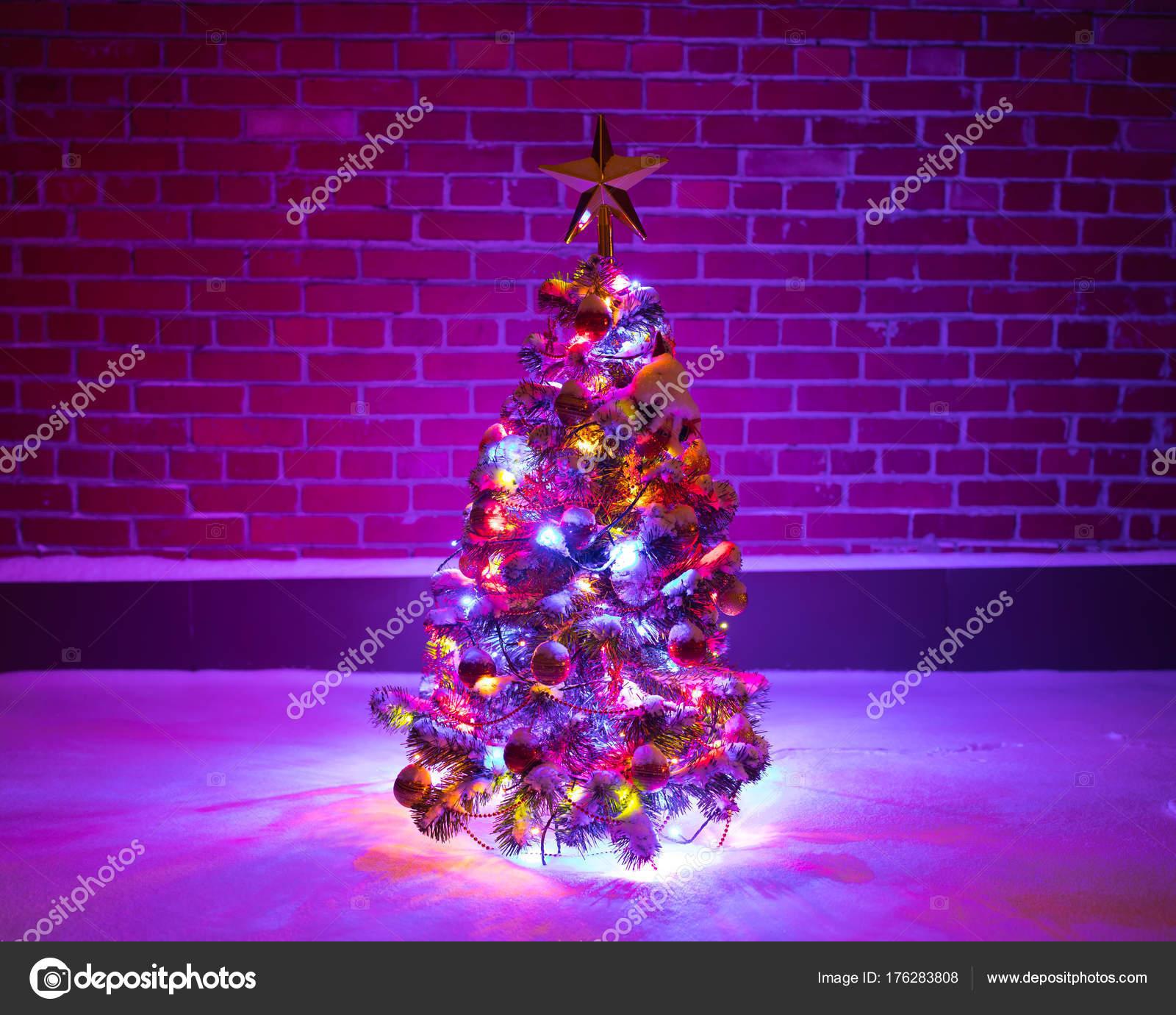 kerstboom met feestelijke verlichting in sneeuw buiten paarse baksteen muur achtergrond stockfoto