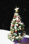 Vánoční stromeček s Slavnostní rozsvícení v sněhu venku, černá noc pozadí