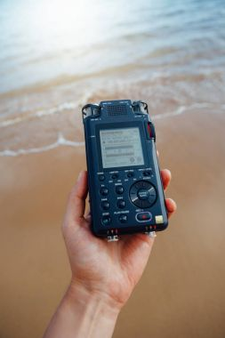 portable audio recorder in hand recording ambient sounds of sea
