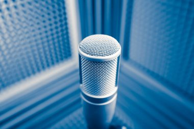 professional microphone in sound recording studio, blue acoustic foam background